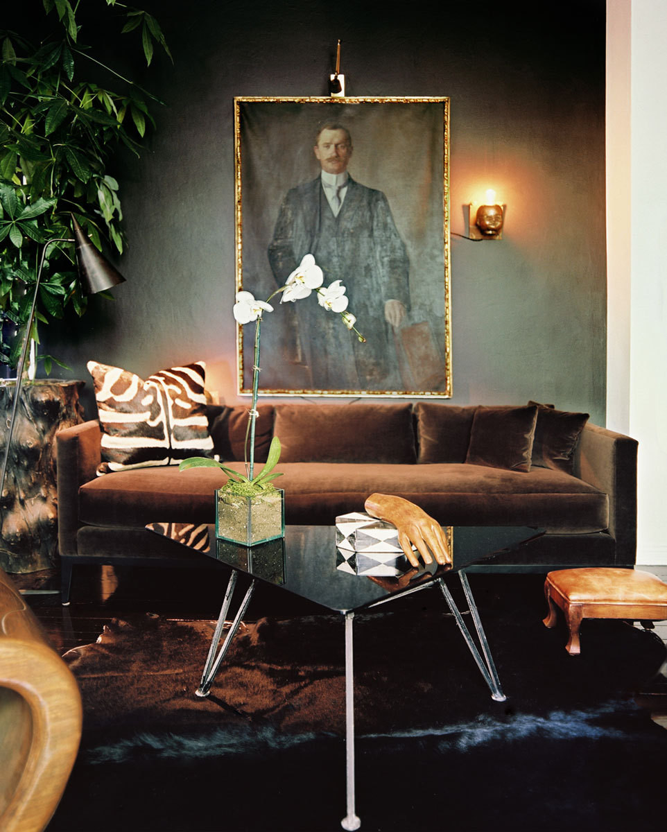 A life-size oil painting juxtaposes a contemporary sofa and a vintage cocktail table.