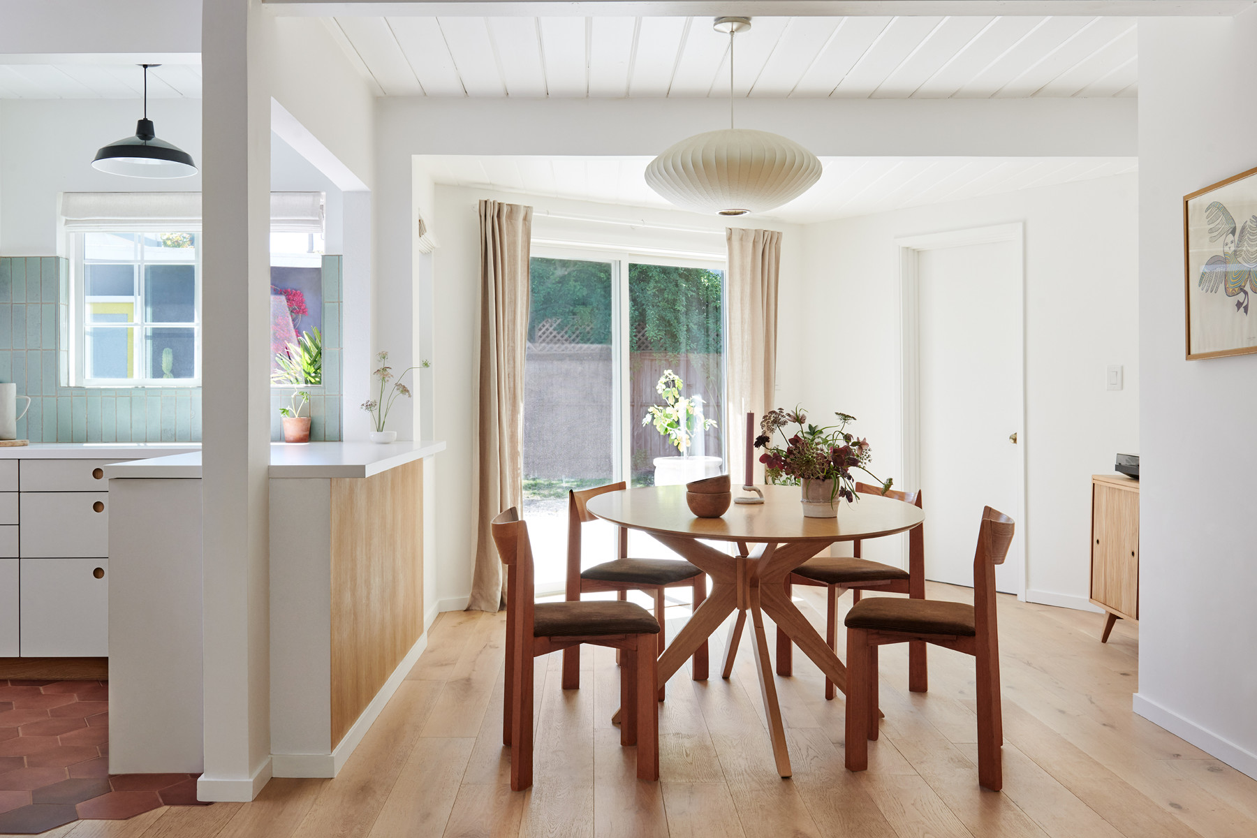 The home's light-filled dining and kitchen area creates a sense of warmth. Craigslist-sourced Table|George Nelson Bubble Pendant| Factory Direct Flooring.