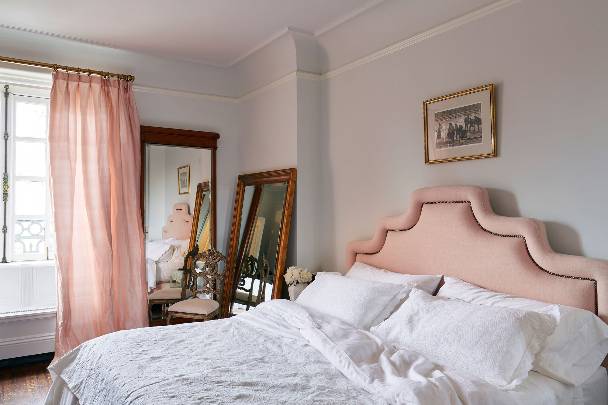 The master bedroom's pink drapery and upholstered headboard are accented with gold finishes and rich, hardwood floors. Two large mirrors sit in a corner to reflect natural light from the windows.