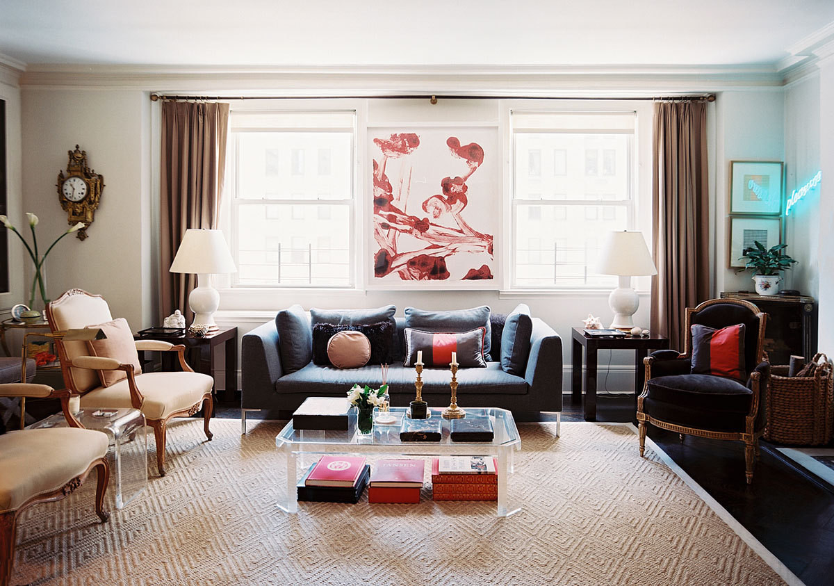 Matching pairs of lamps, brass candlesticks, and antique chairs lend a sense of order to the eclectic blend of living room furnishings. Rather than covering each window with its own set of curtains, the Clarkes visually widened the room with one expansive curtain rod.
