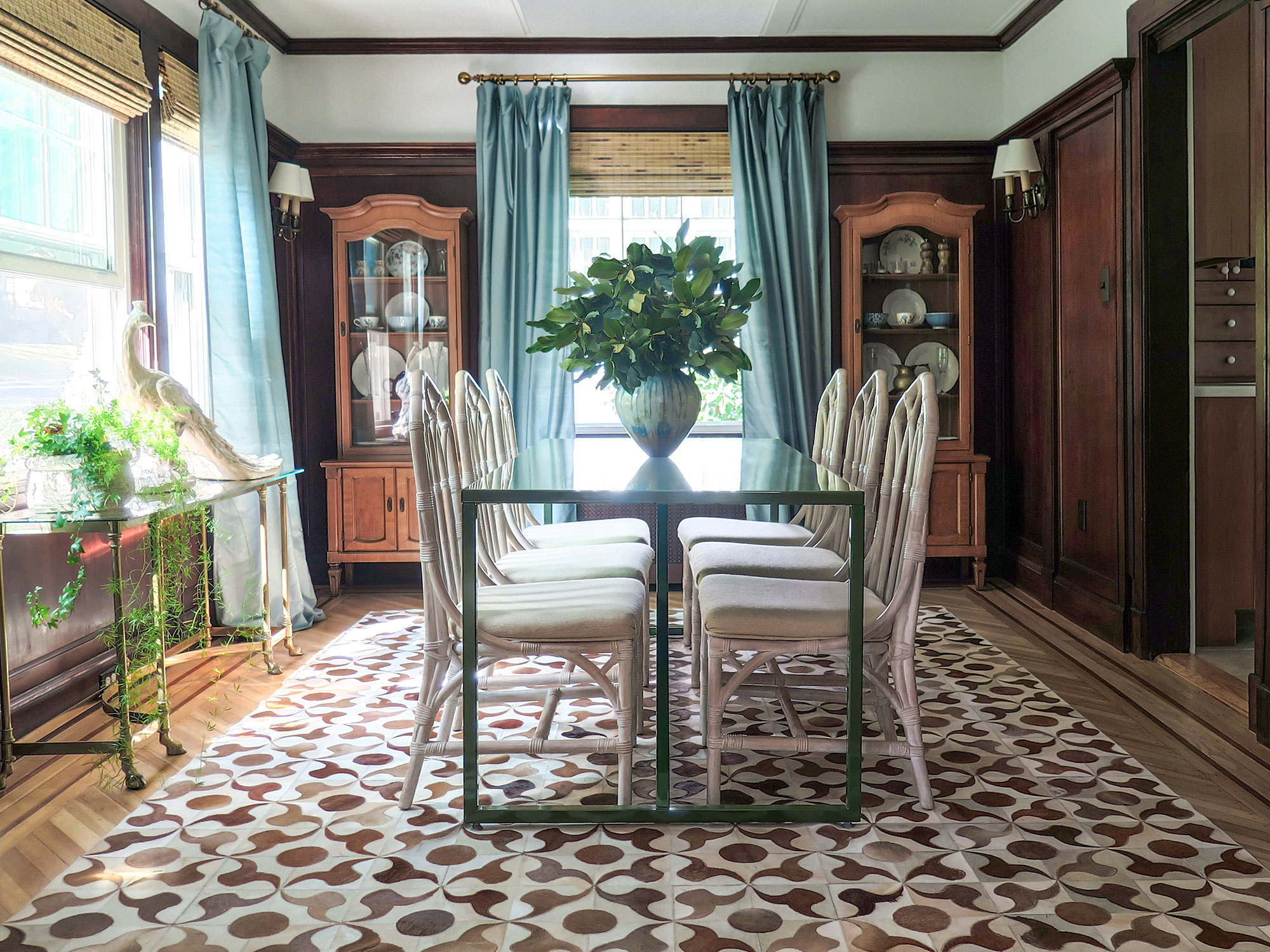 Jill Danyelle of Verdoier gave this 1920s home in South Orange, New Jersey, a modern-day facelift, while preserving its historic charms. In the dining room, wood-paneled walls are balanced by a streamlined table from Blu Dot, a patterned hide rug, and a fanciful faux Peacock sculpture.
