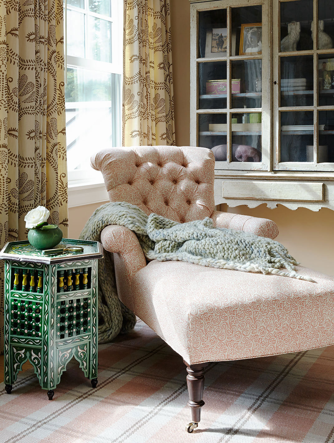 A printed chaise and Moroccan side table animate another corner of the guest room.
