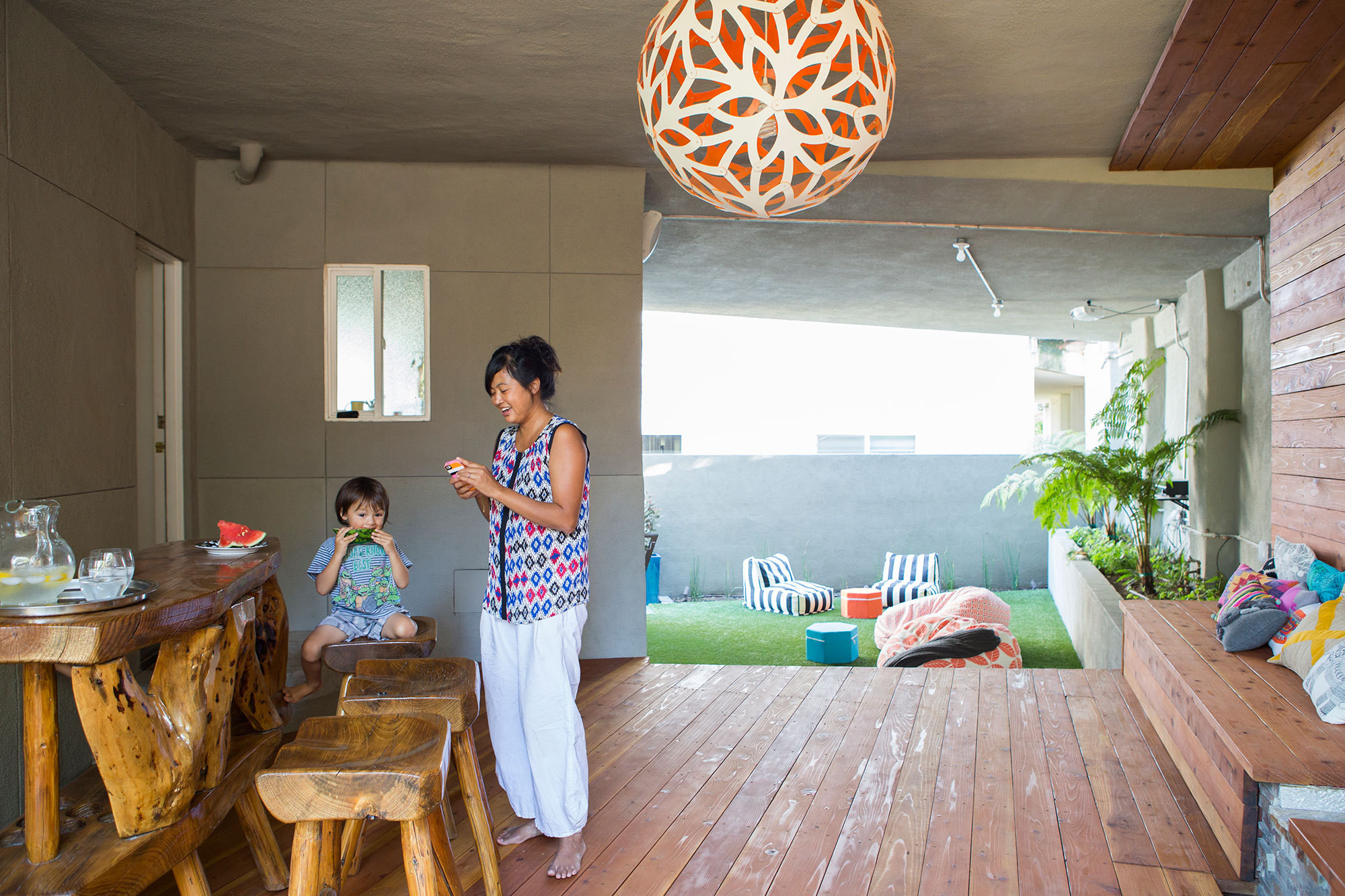 """Haily Zaki with her eldest son, Cael (now five), in the coveredoutdoor living areashe calls """"the Grotto."""" Custom pendant light by David Trubridge."""