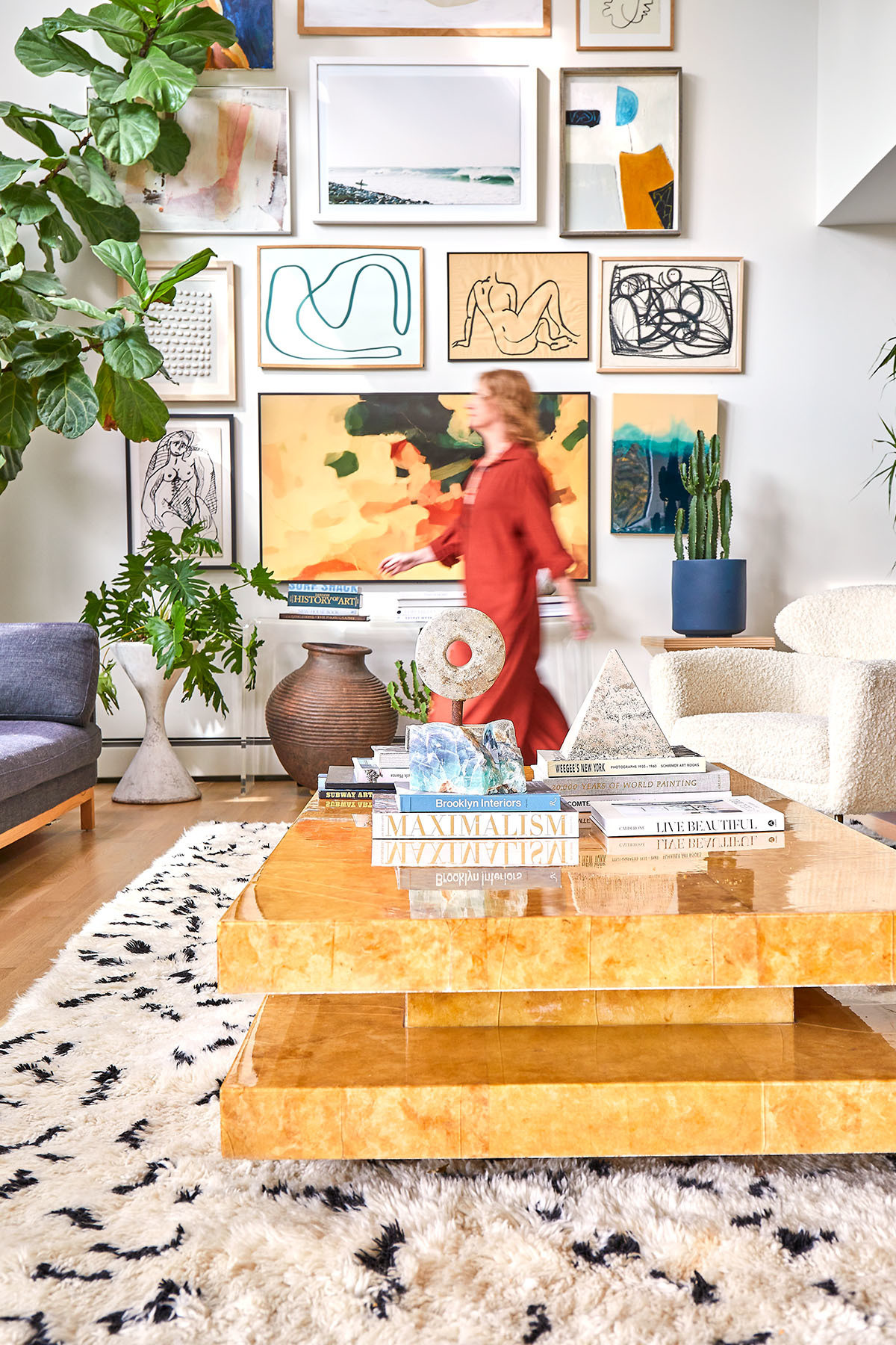 An eclectic gallery wall serves as a mood board for Arasa's Pound Ridge home. Benjamin Moore Paint | Interior Define Sofa | Chairish Vintage Coffee Table | World Market, Patina Studios Assorted Pillows | Aelfie Area Rug | CB2, World Market, Willy Guhl Assorted Planters.