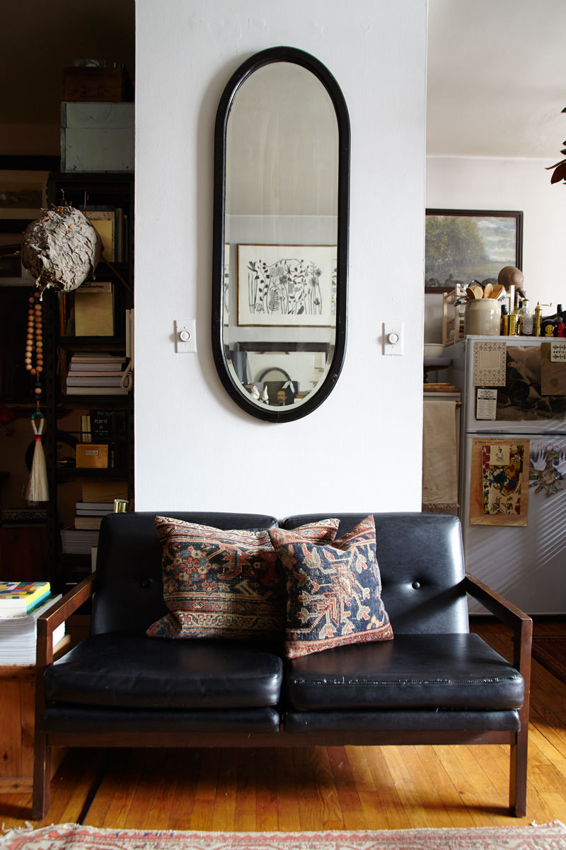 A vintage loveseat gets a hit of texture from throw pillows fashioned out of antique rugs.