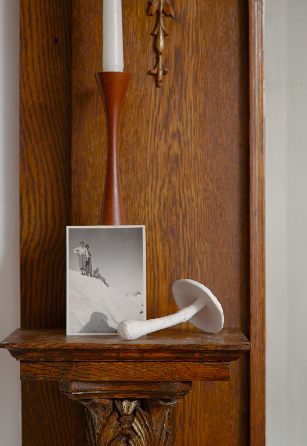 A photo of the author's father scaling the Swiss mountains is set next to a porcelain mushroom and vintage candlestick.