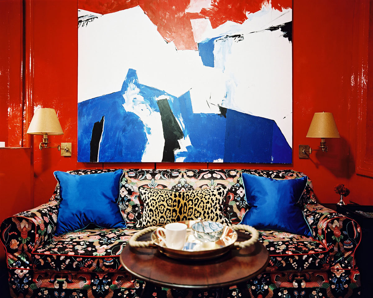 After lacquering his entire living room, kitchen, and entryway in high-gloss red, he applied red piping to his reupholstered couch to tie in the element.
