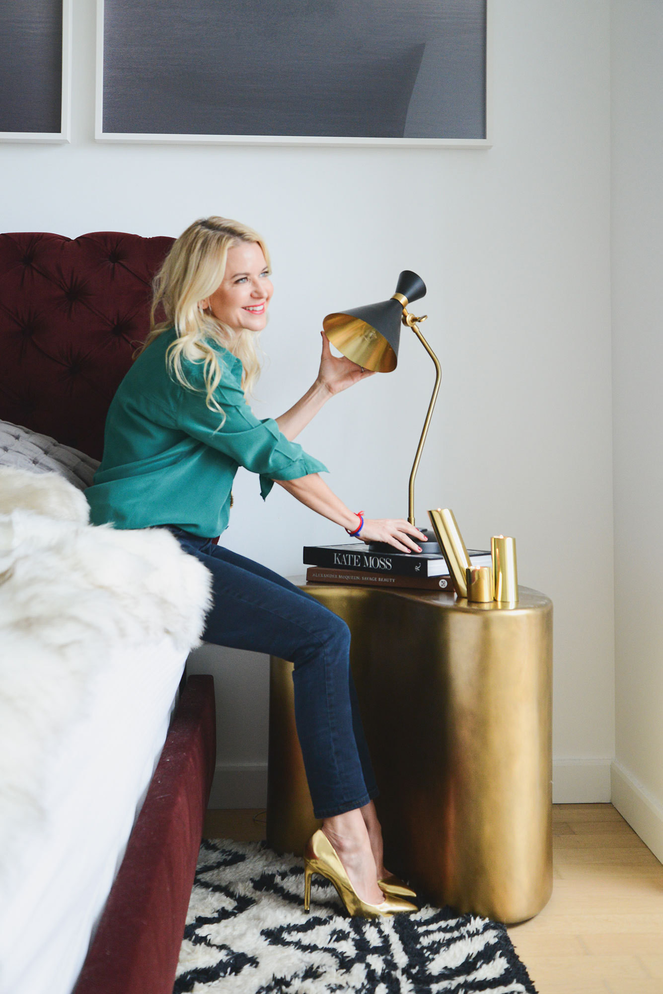 Lemieux makes minor adjustments to a DwellStudio task lamp on a bedside table.
