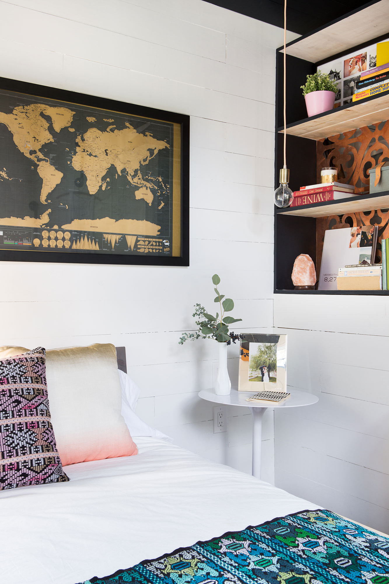 A wall nook for books is also backed by copper paneling; a map above the bed speaks to the owners' interest in travel.