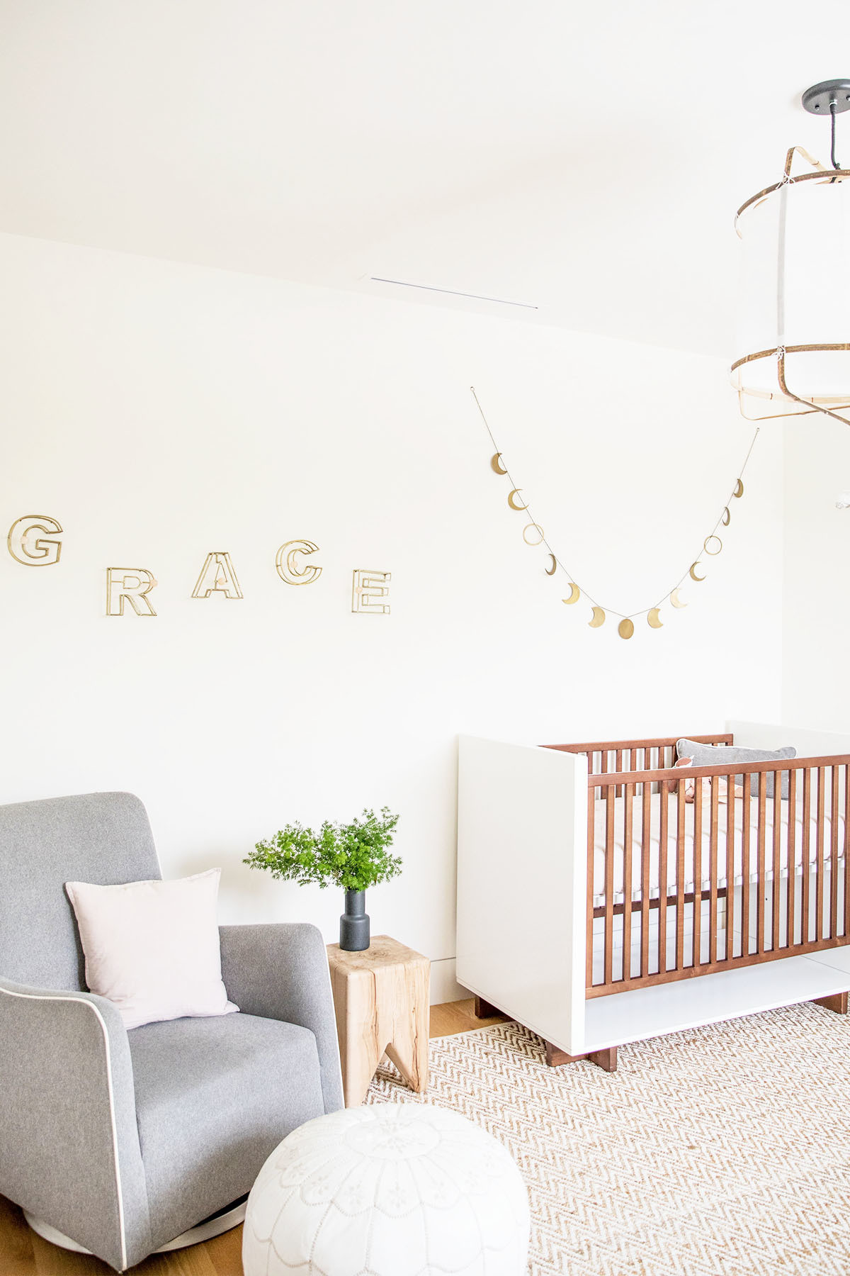 Daughter Grace's nursery is cozy yet minimal, adhering to a gender neutral color palette. Room & Board Crib | Monte Armchair | Serena and Lily Pouf | Matteo Pillow | Kalon Stool | Restoration Hardware Garland | Anthropologie Signage | West Elm Rug | Ay Illuminate Chandelier.