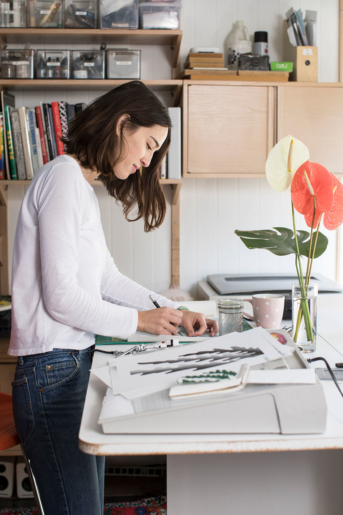 Plambeck — pictured here in her converted studio — emphasizes the significance of having a dedicated workspace, away from the primary living areas. Benjamin Moore Paint | Vintage Shelving Unit | Eric Plambeck Custom Standing Desk.