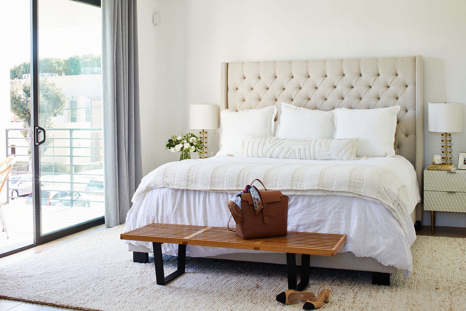 Neutral tones are layered with textured pieces to add dimension and visual appeal.Restoration Hardware Chesterfield Fabric Panel Headboard |Restoration Hardware Linen Duvet Cover |NelsonPlatform Bench |Scenario Banded Glass Table Lamp |Target Euro Pillow |West Elm Mini Pebble Wool Jute Rug.