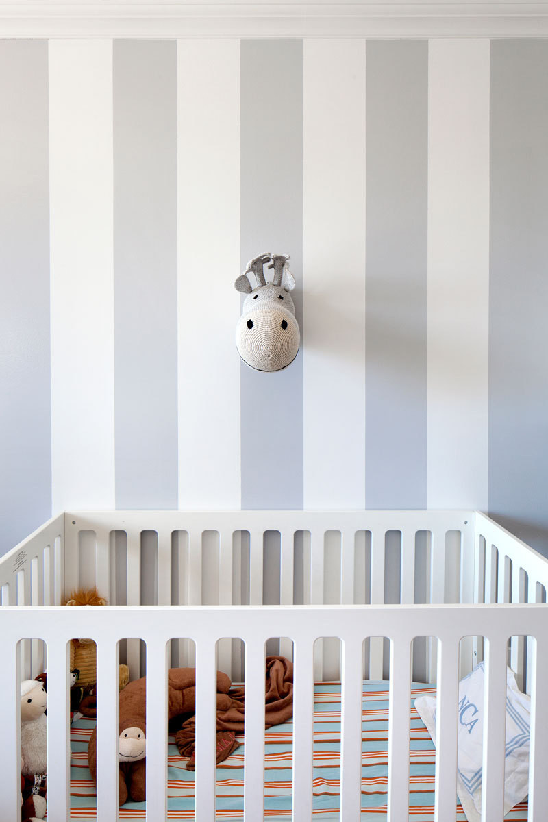 In two-year-old Noah's room, a knit animal trophy by Anne-Claire Petit accents gray, awning-striped walls
