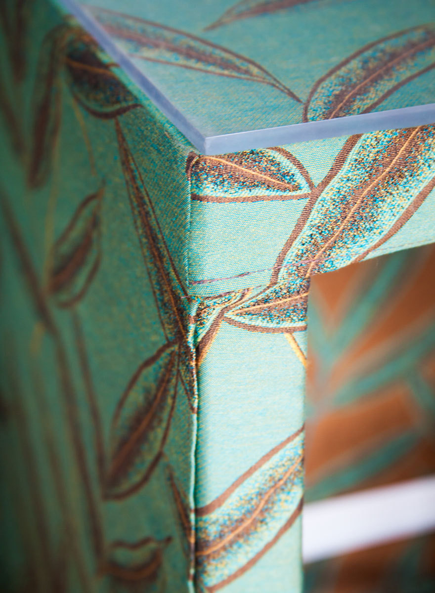 """The desks are """"slipcovered"""" in a rich green fabric."""
