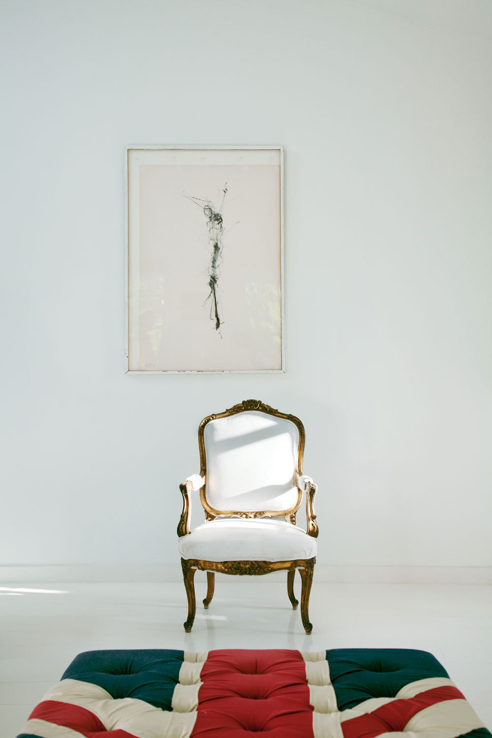 """The simplicity of this scene says so much. The dancer in her frame, the Union Jack ottoman, and the gilt-edged Louis XV chair, reupholstered in Sunbrella fabric to stand the test of wet bikini bottoms."""