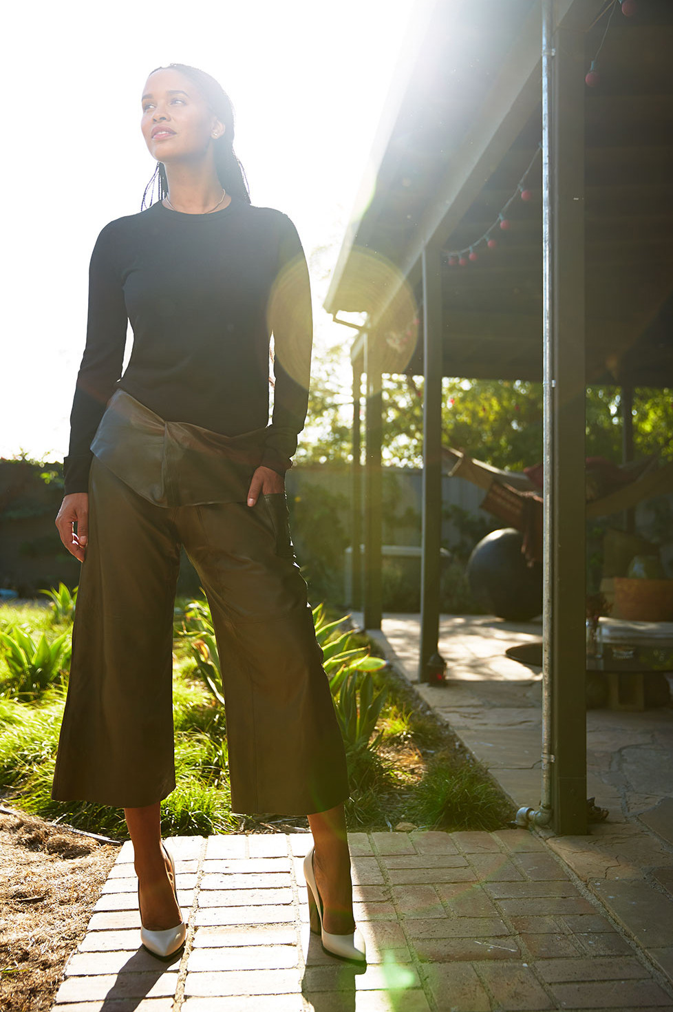 In the backyard, wearing a military-green cropped Eden Pant from Basic Terrain, a Tibi shirt, and Greymer heels.