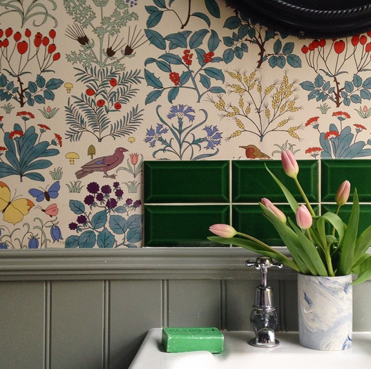 Emerald beveled subway tiles and printed botanical wallpaper in his London home.