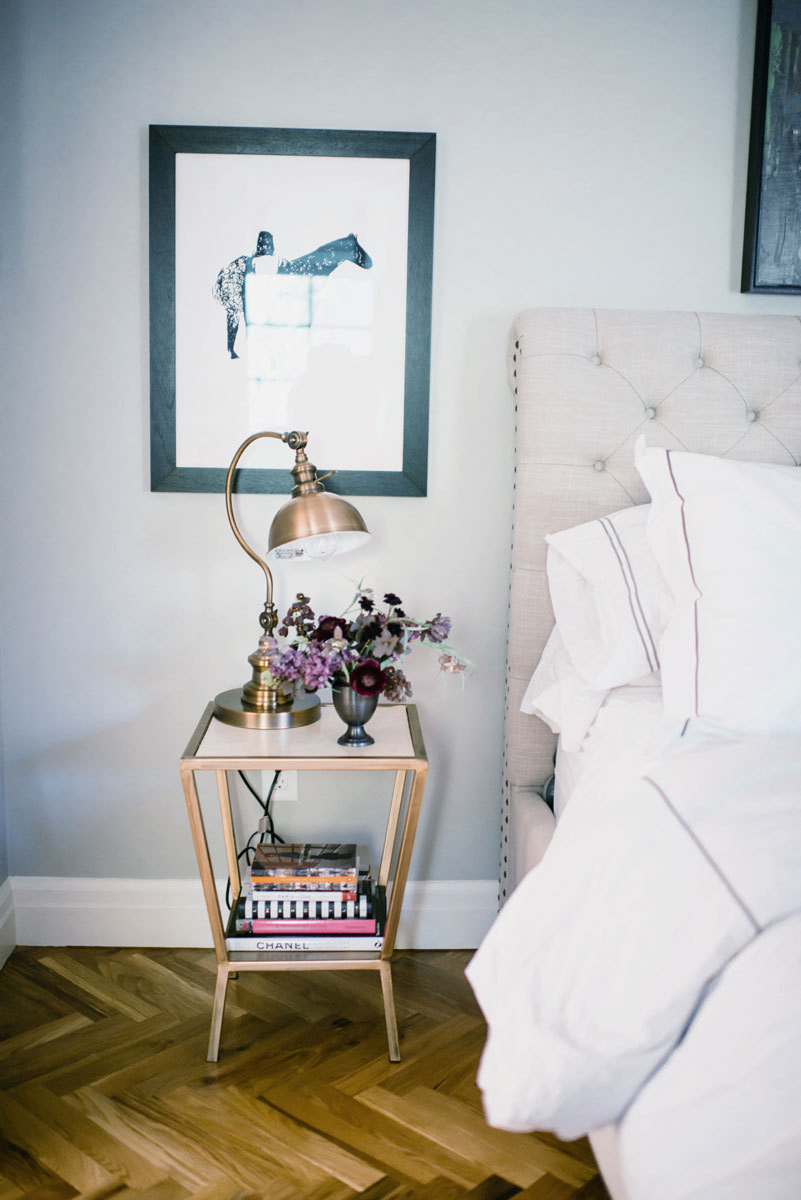 The master bedroom's eclectic mix includes lighting from TJ Maxx, night stands from Target, and a tufted headboard from Pottery Barn.