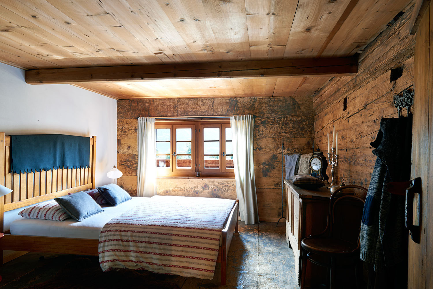Wood-paneled walls, ceilings, and windows reinforce the mood of rustic comfort in the master bedroom.