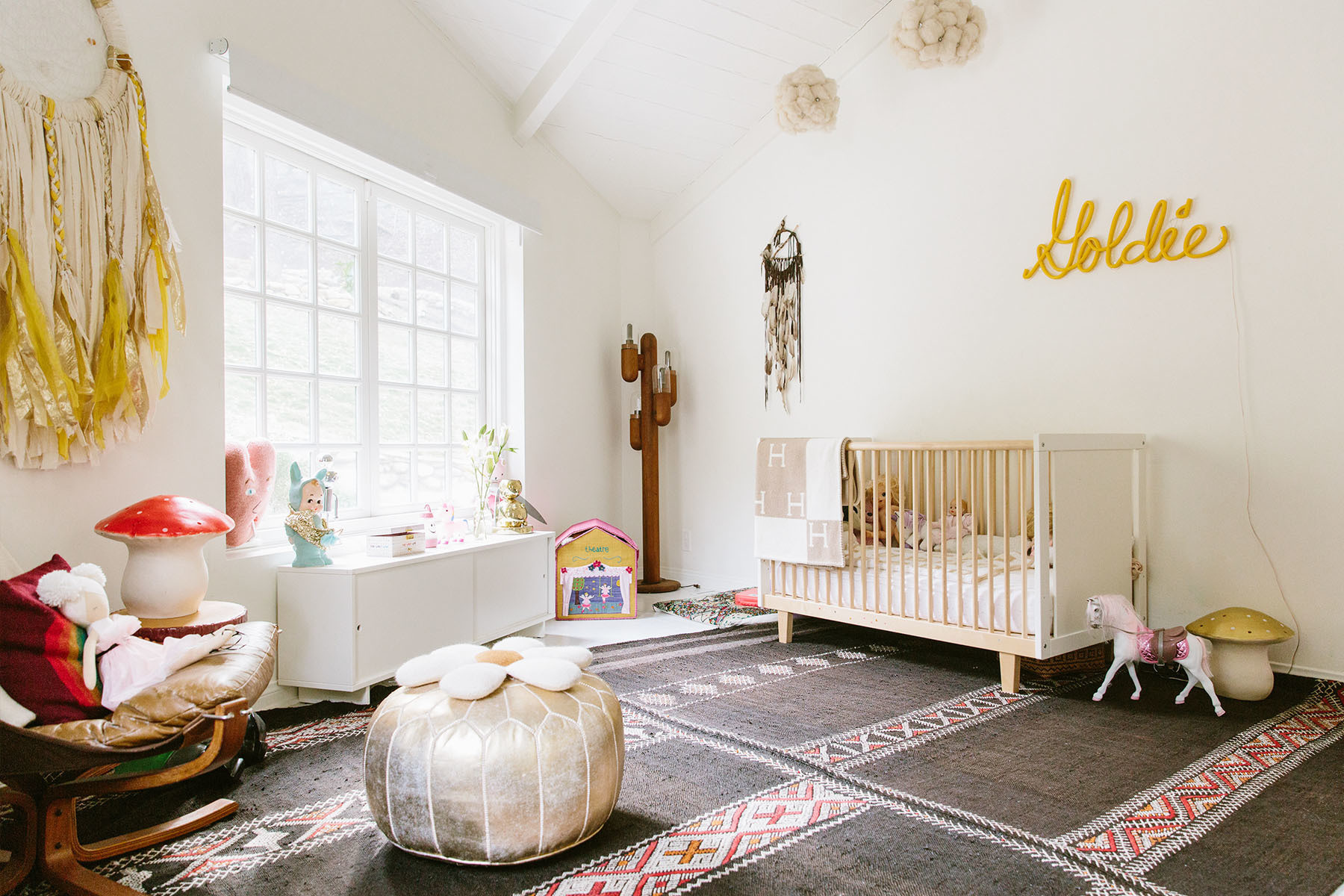 The duo stuck to a yellow and gold color scheme when designing the ideal space for their daughter, Goldie. Oeuf Crib | Light Installation, Dream Catcher, couples' own design | Vintage Toys, Pouf.