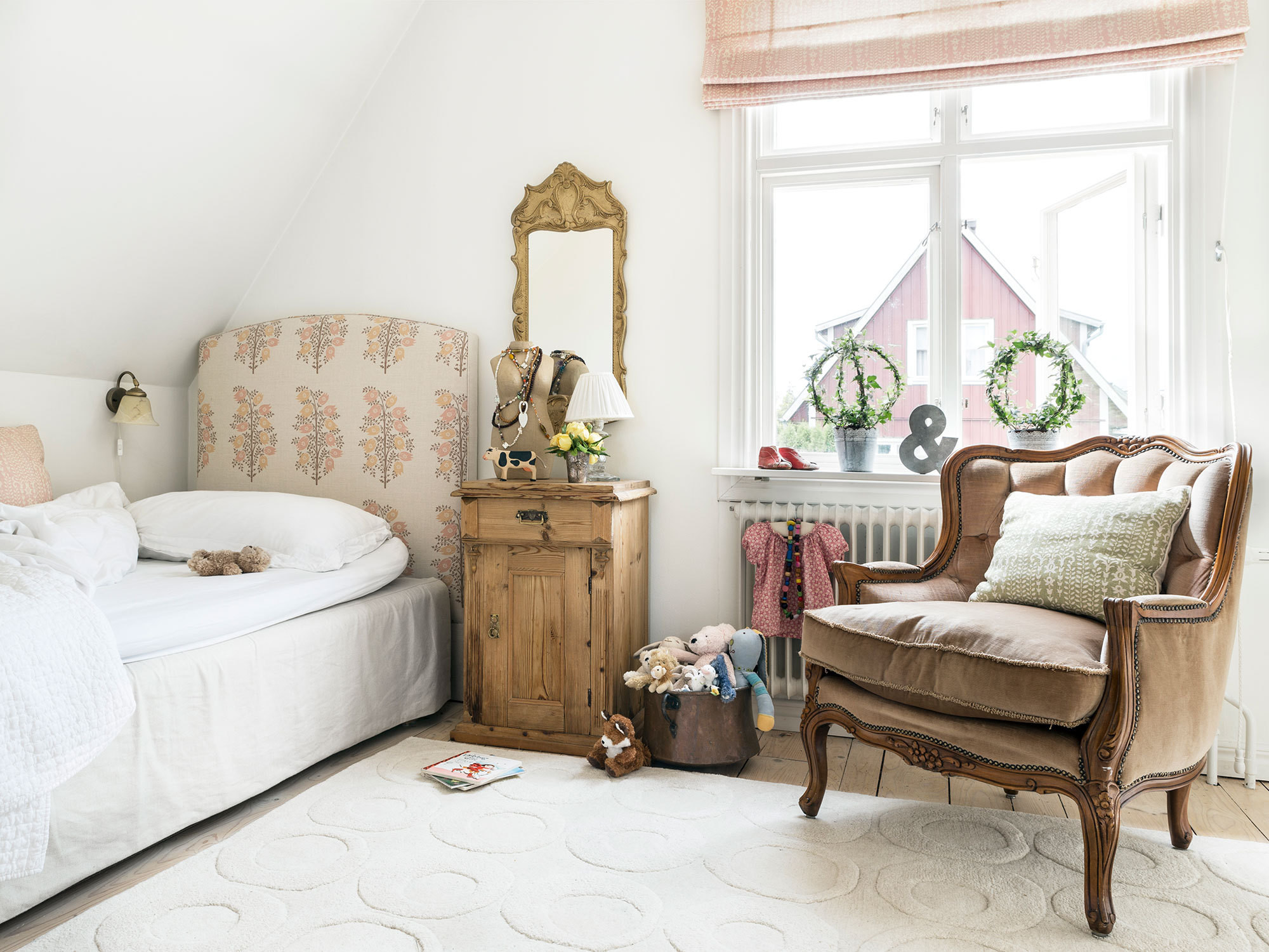 Liv's bedroom features designer fabrics (including Raoul Textiles on the headboard and Roman shade) and well-chosen antiques.
