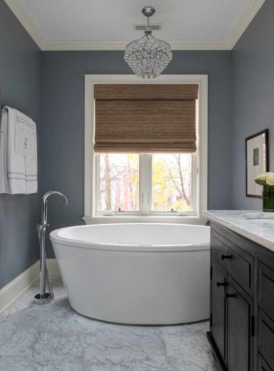 A freestanding tub beneath a glowing chandelier is the couple's master suite indulgence.