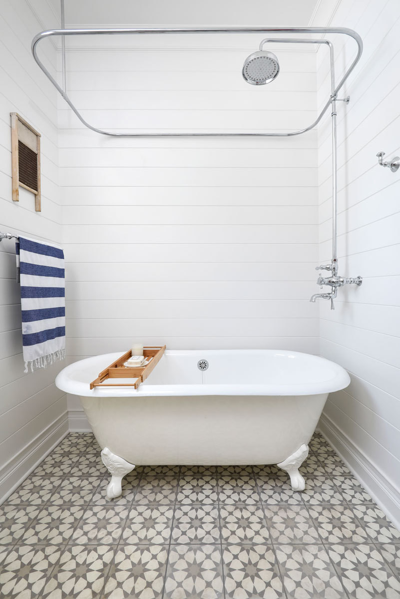 The first floor bath includes a classic claw foot tub and simple shiplap walls.