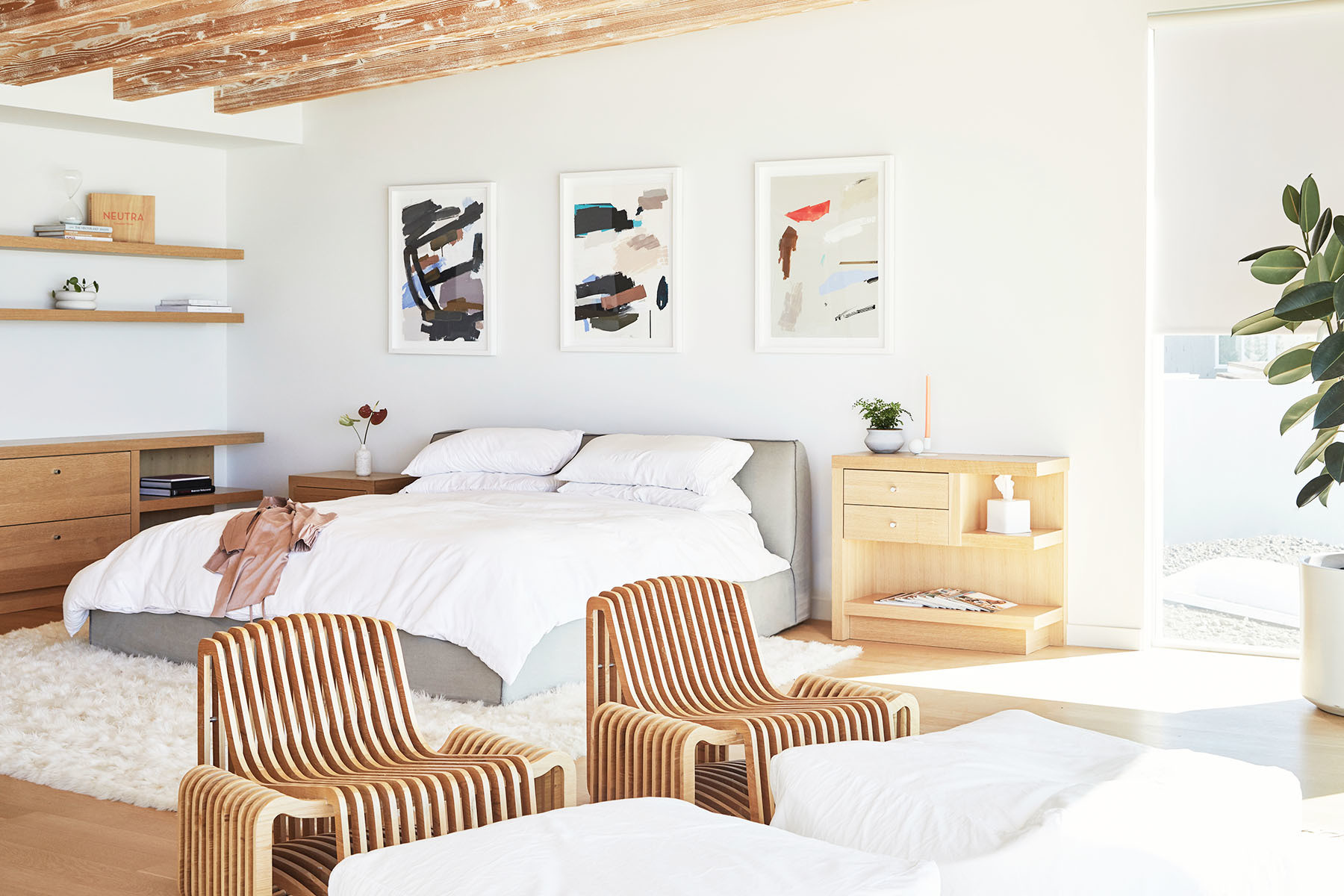 This entrepreneur's Malibu beach house is a breath of fresh air. Custom Bed | Karina Bania Triptych via Uprise Art | Custom Side Tables | Custom Shelving | Vintage Armchairs | Restoration Hardware Bedding | Taschen Book | Garmentory Accent Pieces | Maaari Ceramics | Joss & Main Rug | Lunya Robe.