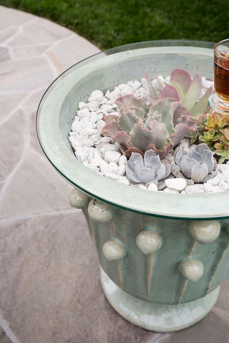 Succulents echo the container's soft hue.
