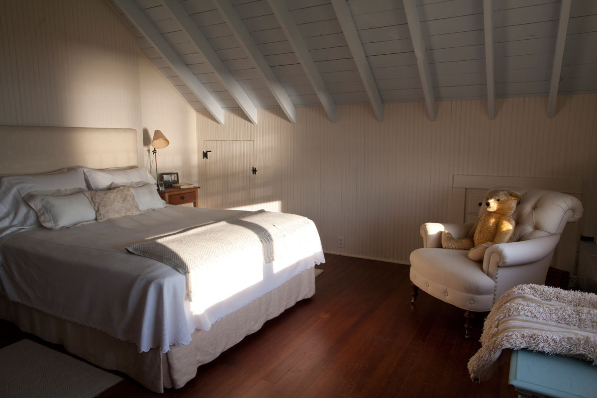 The master bedroom features its original rafters, beadboard, and built-in drawers.