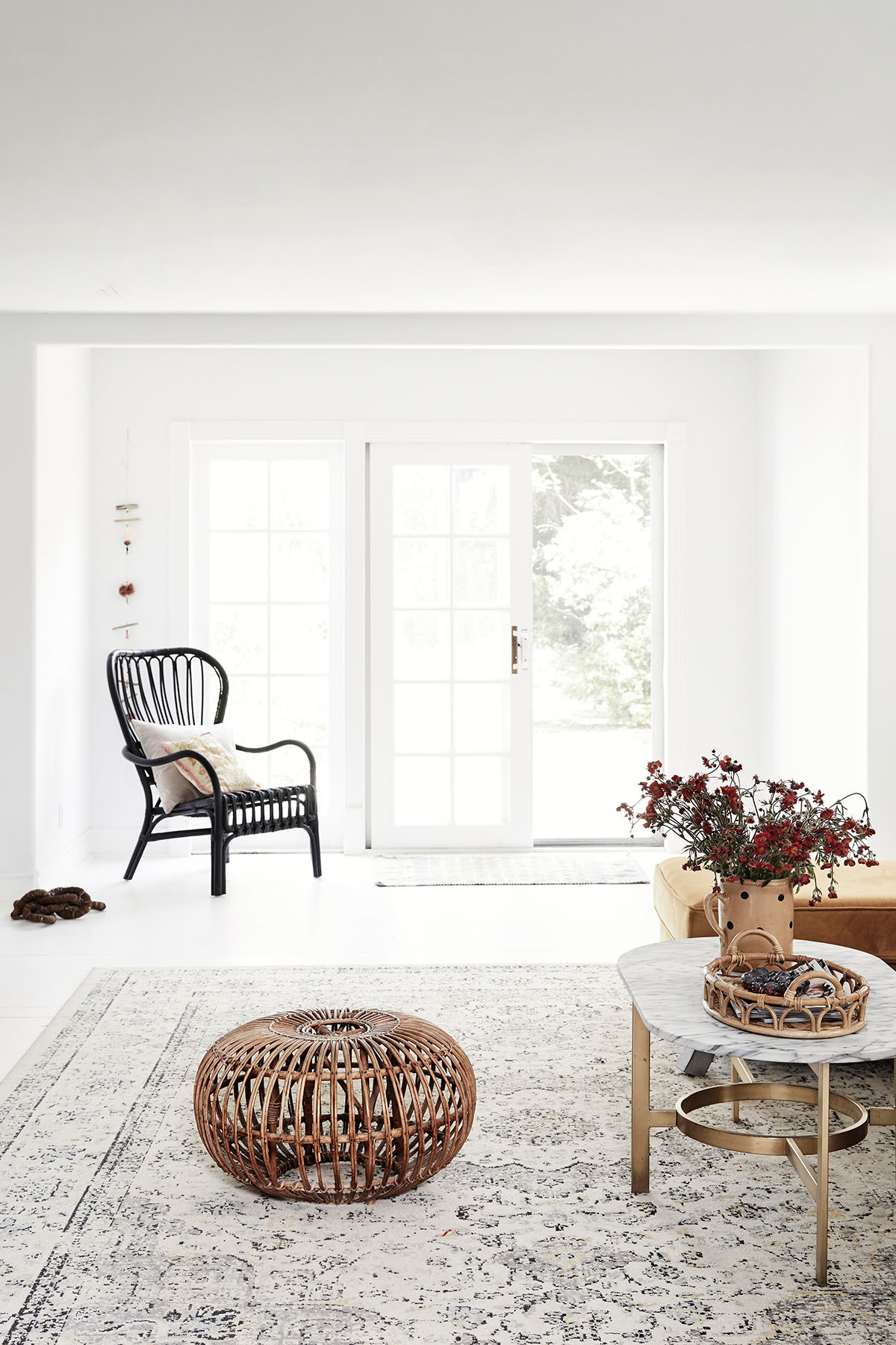 Expansive sitting rooms, repurposed furniture, and white walls and floorboards create an almost gallery-like appeal. IKEA Armchair | Franco Albini Vintage Ottoman | West Elm Coffee Table | Target Tray | Craigslist Vintage Rug.