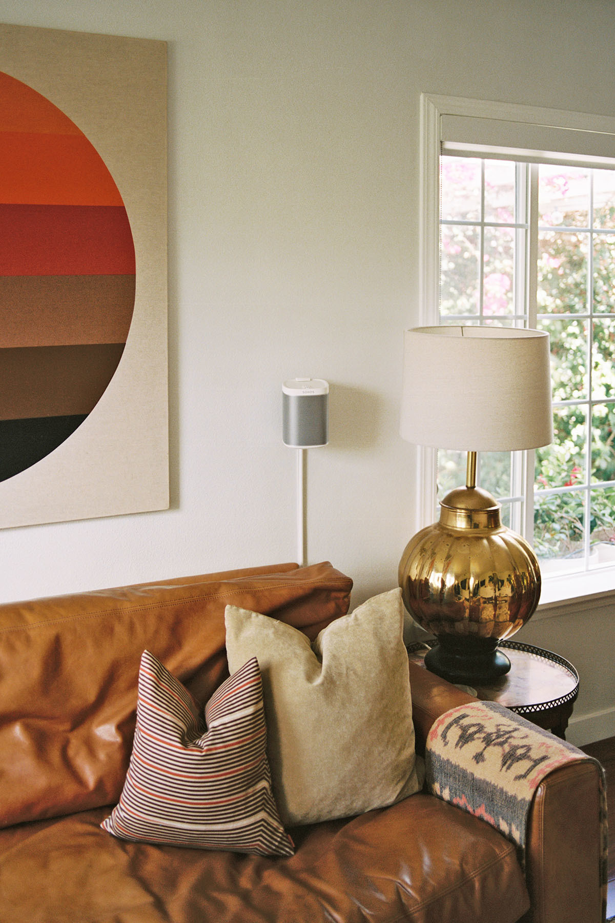 A well-wornRestoration Hardware sofa and sourced sentimental accents complete Madison's open living area.Missoni Home Throw Pillow |Urban AmericanaVintage Artwork | Vintage Table Lamp |Craigslist Side Table.