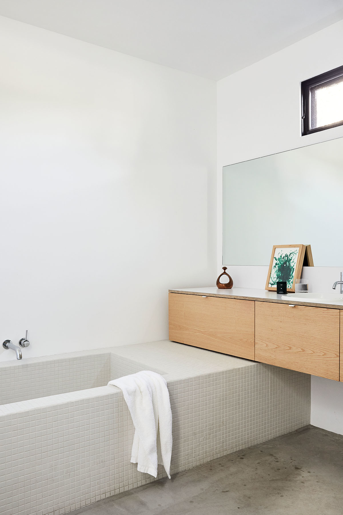 A minimal bathroom — complete with a small scale, dove gray tiled bath and concrete floors — achieves a sense of calm. Seed Probiotics.