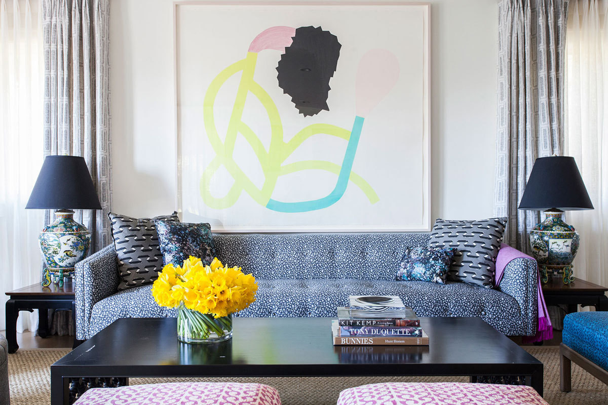 An abstract artwork by Jaime Angelopoulosis displayed prominently in the living room over a sofa covered in a Casamancetextile.