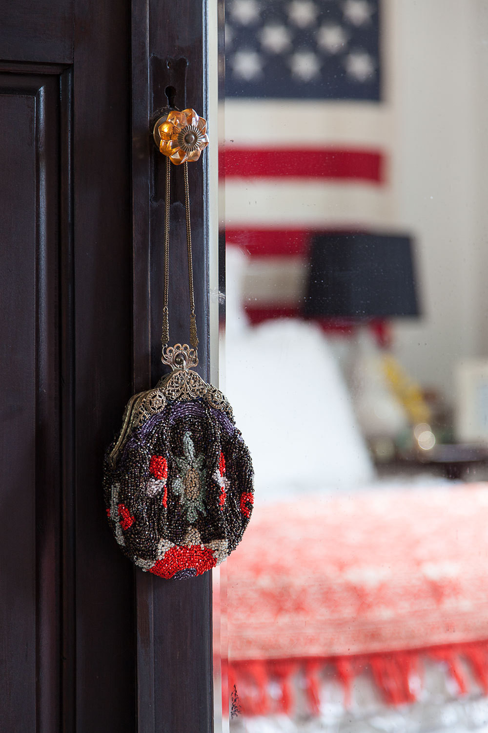 A delicate beaded handbag hangs from an amber-glass knob on the bedroom door.