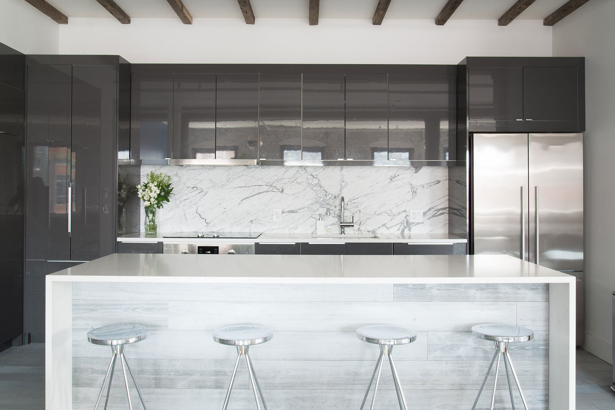 The streamlined kitchen, in glossy gray and marble, provides a visual balance to the many bold design choices.