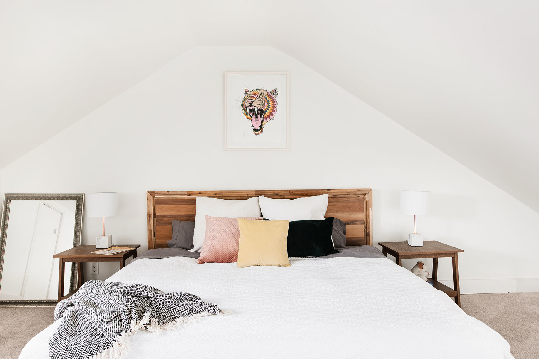 Inside Dineen's artfully cozy master bedroom. Structube Bed | H&M Home Pillows | Kelsey Brookes Artwork | IKEA Side Tables | Vintage Mirror.