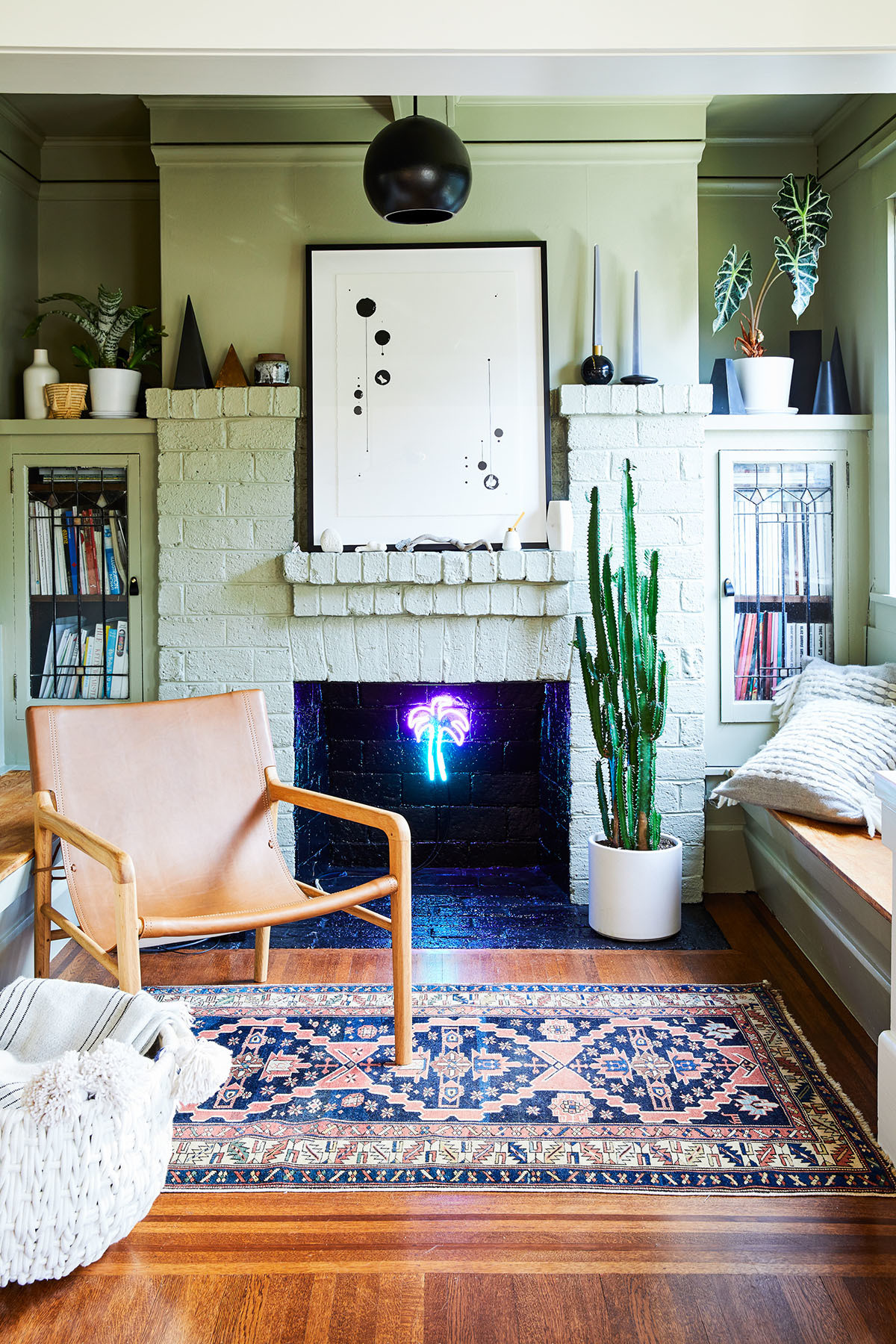 The revamped fireplace room now serves as a funky reading nook. Farrow & Ball Paint | Skye Schuchman Art | Rejuvenation Pendant | ABC Carpet & Home Rug | Barnaby Lane Armchair | Serena & Lily Pillows | Serena & Lily Basket | Meryl Pataky Neon.
