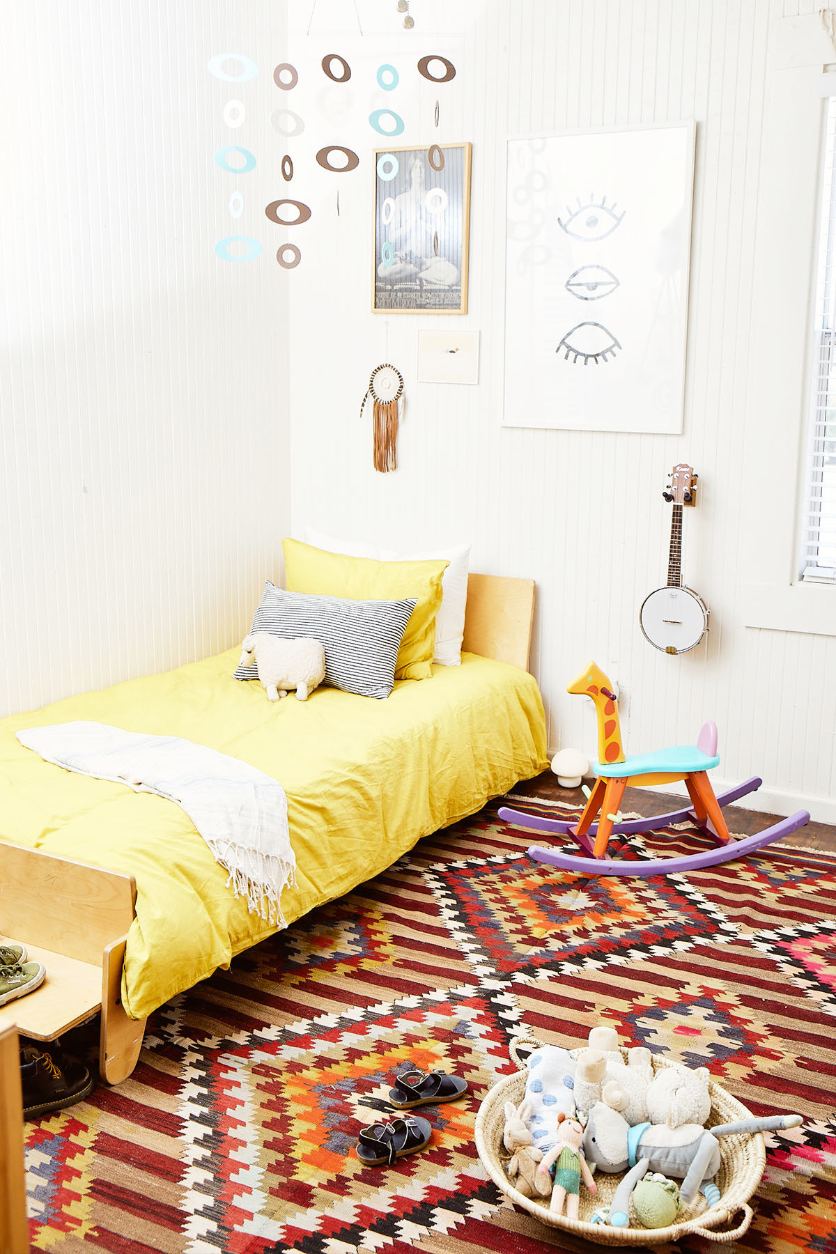Felix's bedroom is decorated with a blend of accessible finds and family treasures, dating back decades.Craigslist Bed |H&M Bedding | Vintage Turkish Rug | Vintage Mobile | Vintage Artwork | Vintage Rocking Horse | Vintage Poster.