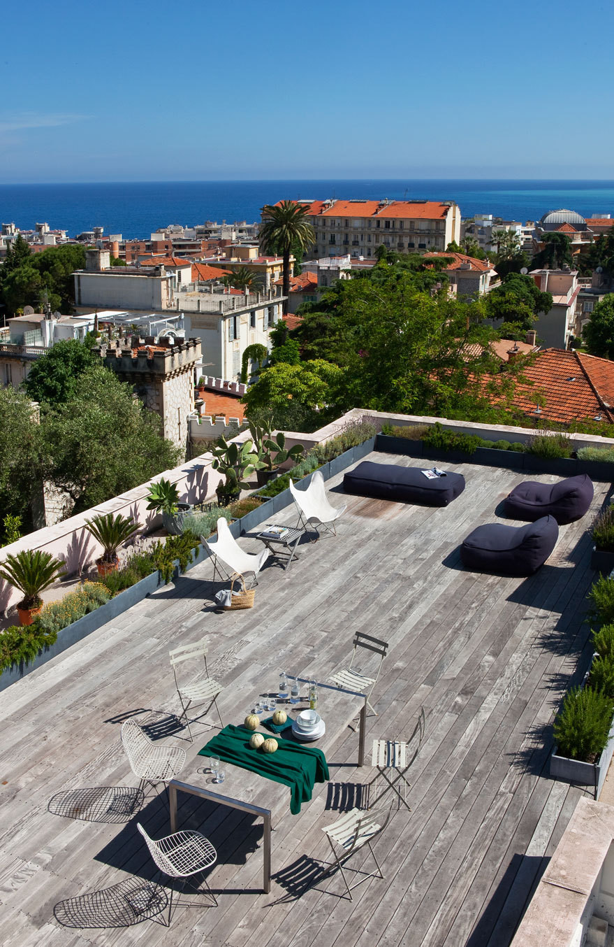 An expansive terrace overlooks the rooftops of Nice, with the sea beyond.