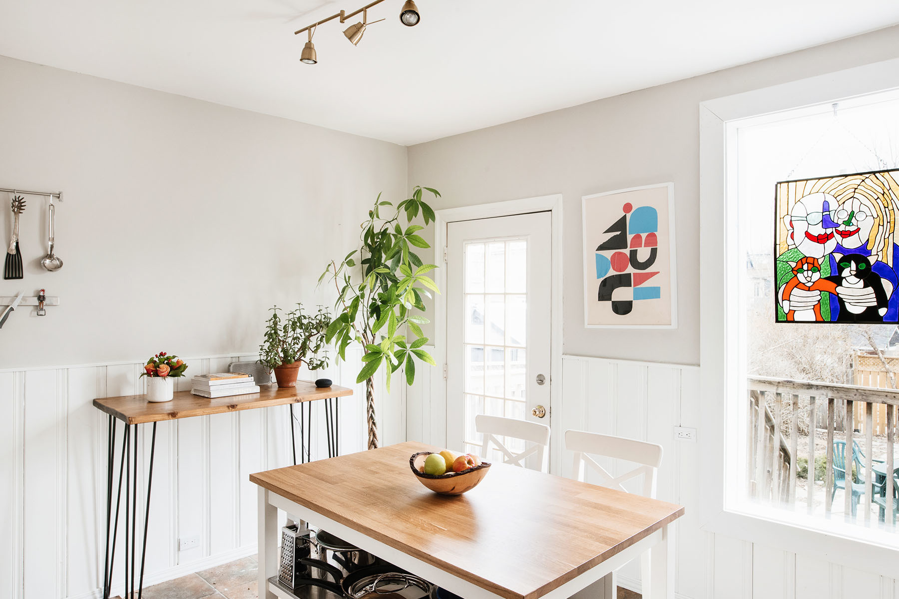 The couple's open kitchen boasts a restorative, contemporary farmhouse look and feel. IKEA Kitchen Island | IKEA Bar Stools | Structube Light Fixture | Custom Console Table | Cody Hudson Artwork | Max Parr Custom Stained Glass.
