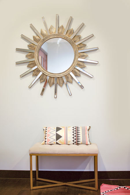 A starburst mirror and neutral-tone ottoman are geometric pieces further enlivened by the patterned pillow and rug.