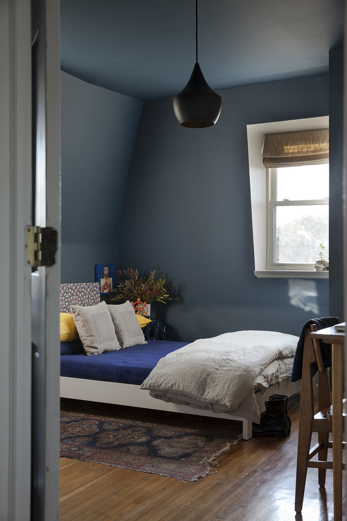 The room, painted in Farrow & Ball's Stiffkey Blue, with a sculptural pendant light from Tom Dixon.