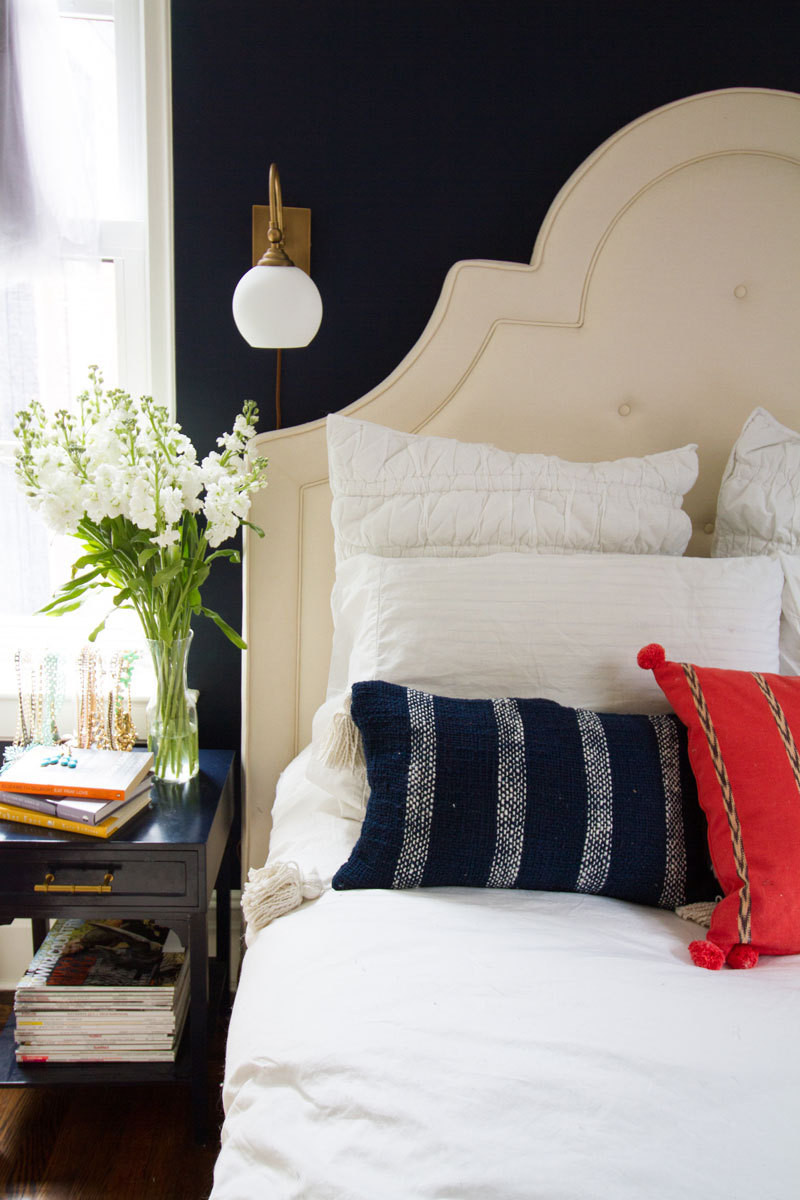 In the bedroom, an elegant cream headboard balances dramatic, navy blue walls.