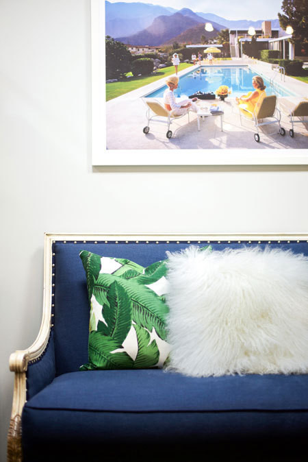 Slim Aarons's Poolside Glamour pops above a navy linen sofa from One Kings Lane. Banana Palm Pillow, Lulu & Georgia.