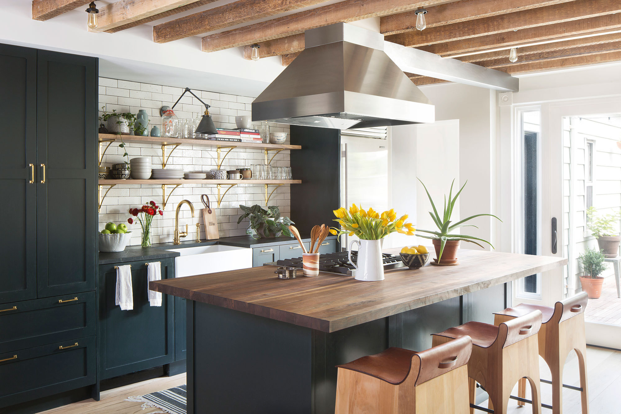 Designer Alison Jennison's townhouse kitchen makes a high-contrast statement with cabinetry in Benjamin Moore's Dark Knight set against crisp subway tile and gleaming metallic accents.
