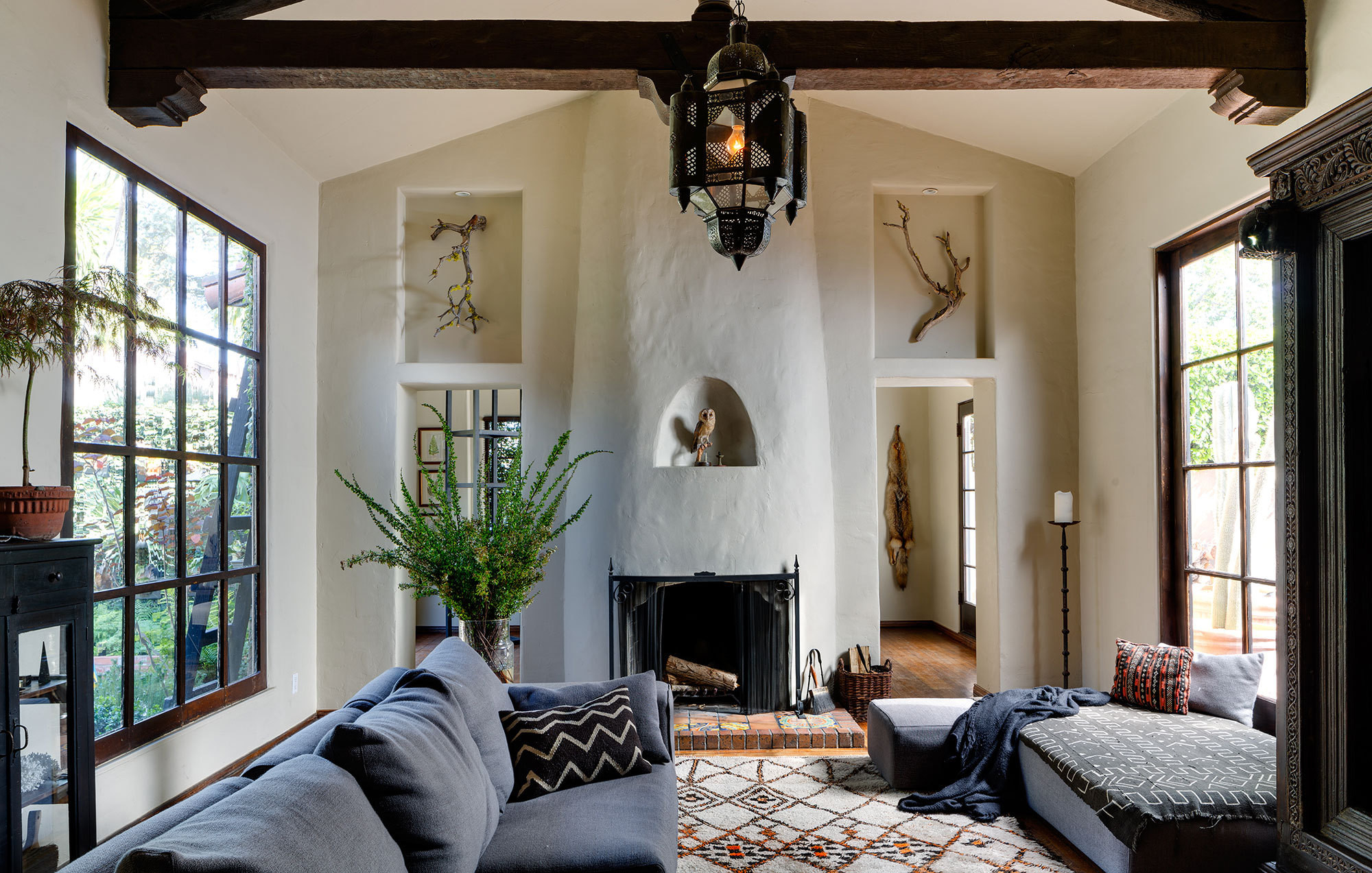 In the sunken living room, wall niches display sculptural objets from nature and draw attention to the high ceilings and handsome wood beams.