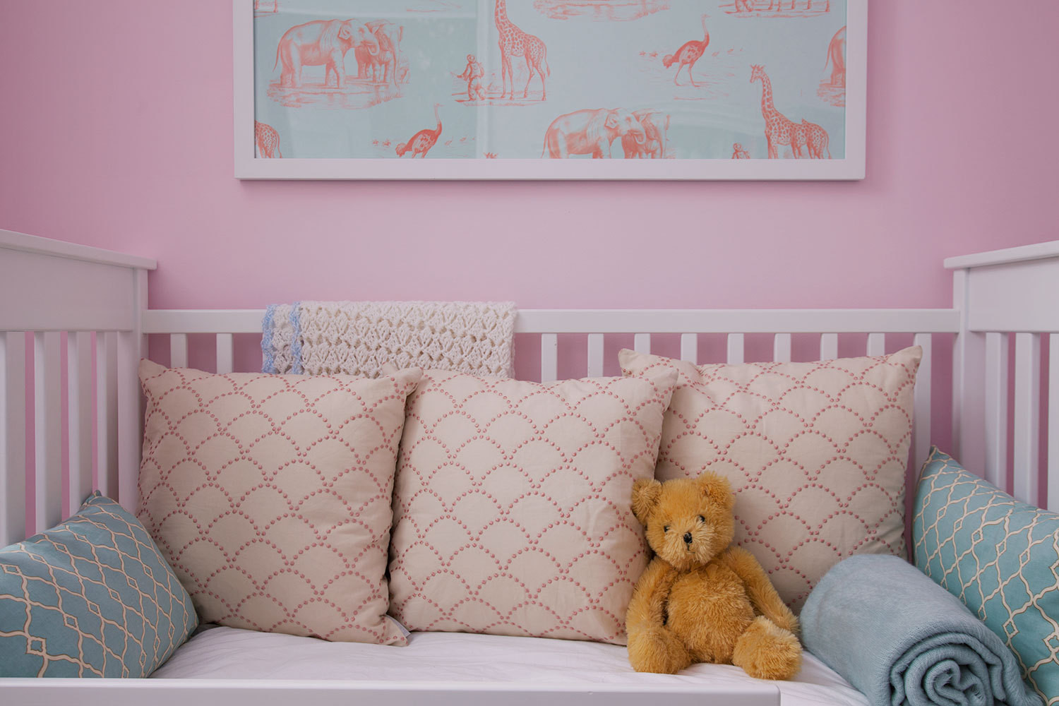 Soft teal lumbar pillows and a orange stuffed bear mimic the hues of the framed Abnormals Anonymous wallpaper.