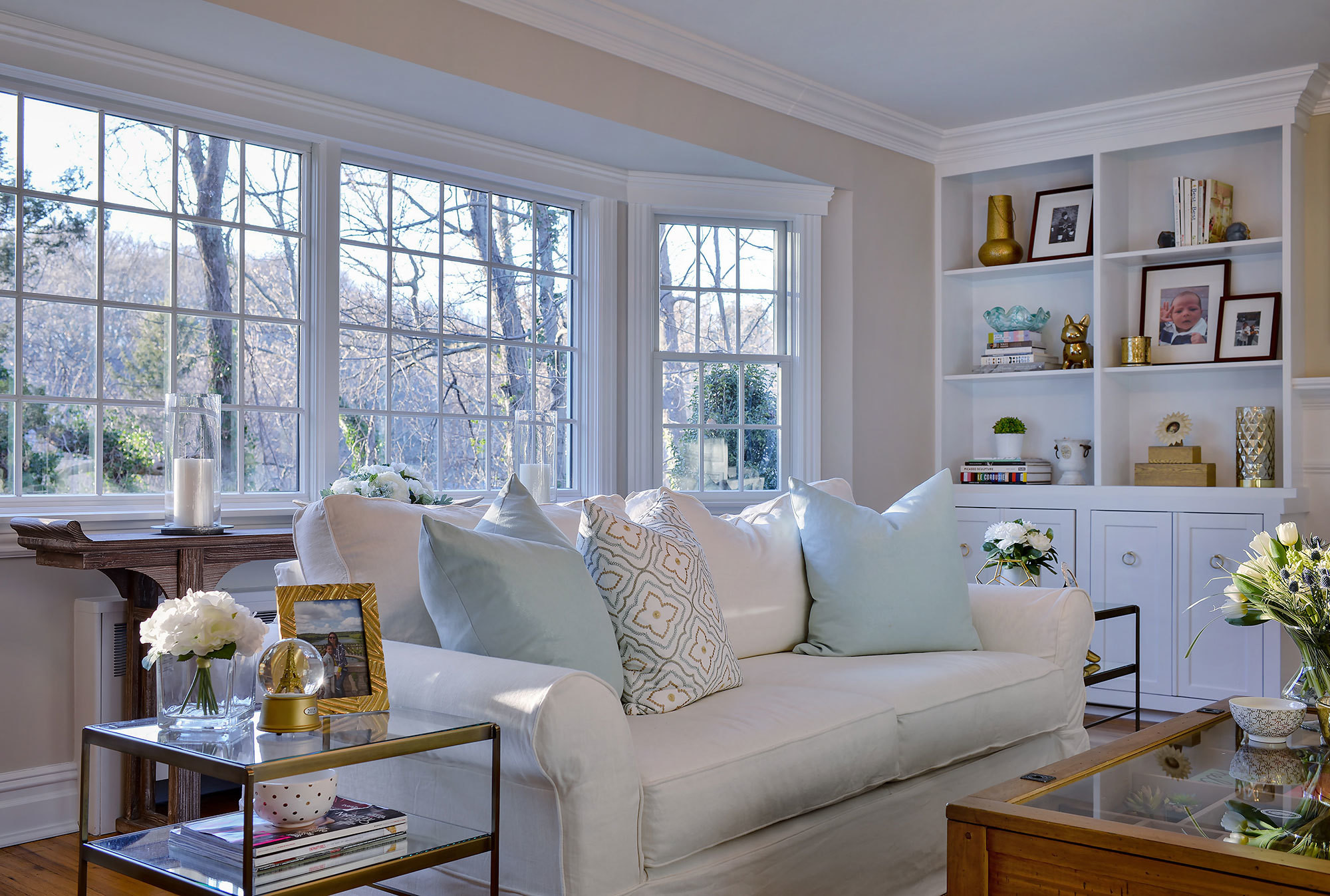 Sun-filled windows drench the main living space with natural light, highlighting the room's built-in bookshelves and plush seating, while also providing verdant views of the home's expansive property.