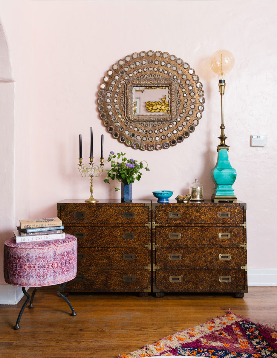 Colorful accents coordinate with an ornate mirror and angular campaign chests in the living room.